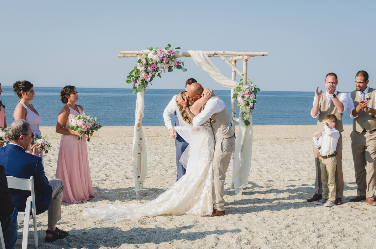 photo of bride and groom hugging after wedding ceremony on the beach at Pavilion at Sunken Meadow