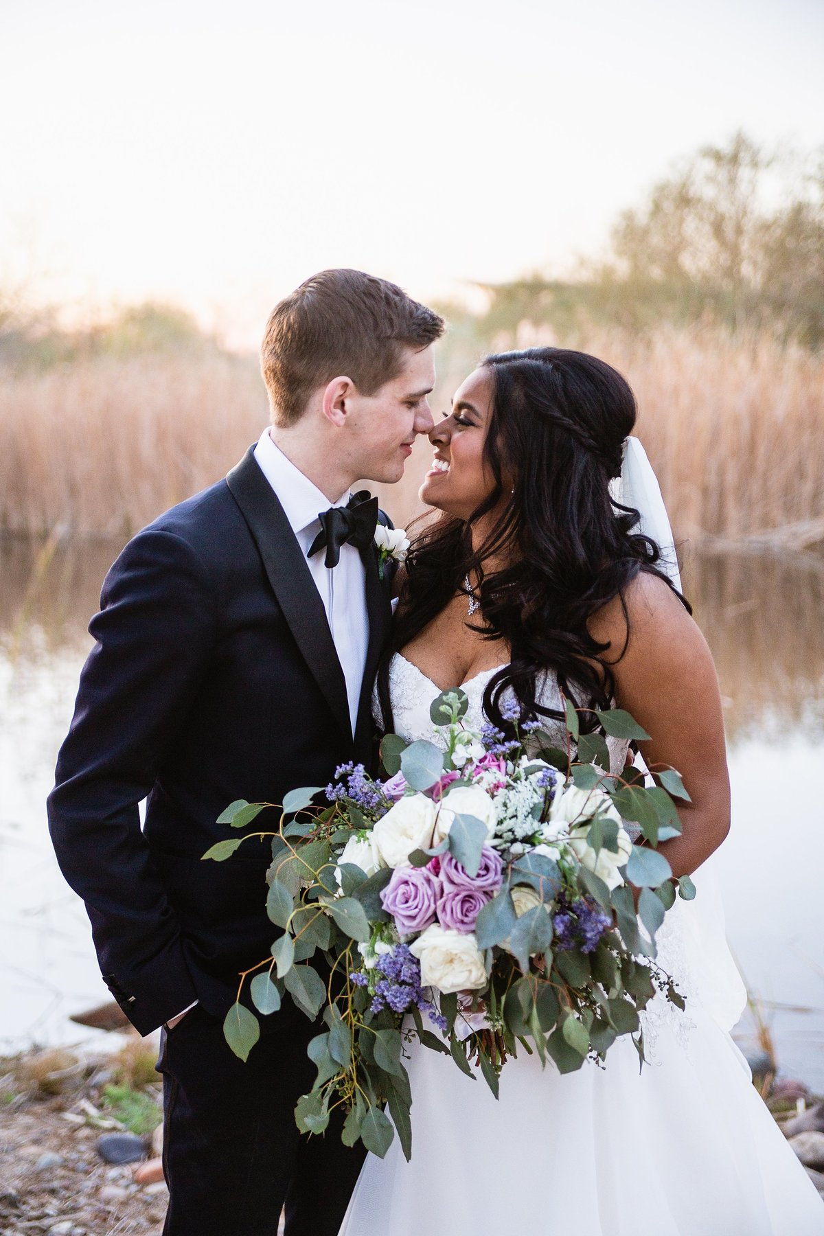 Bride and groom share a romantic moment at their desert wedding by Phoenix wedding photographer PMA Photography.