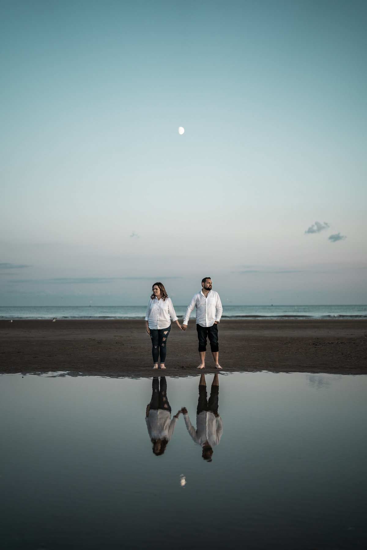 Engaged couple and their reflection on Camber Sands beach,