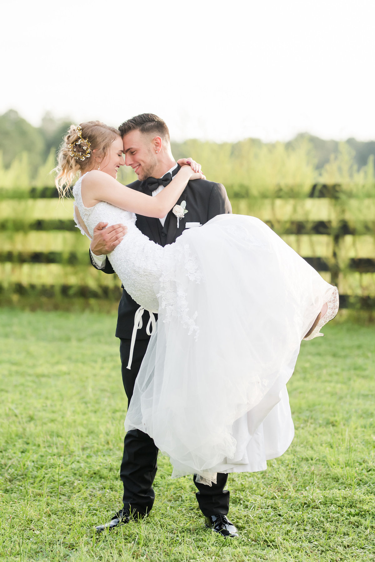 Groom picks up bride in cradle in a field
