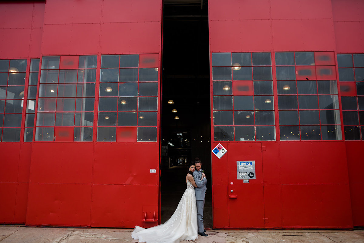 Bride and Groom in front of red hangar doors