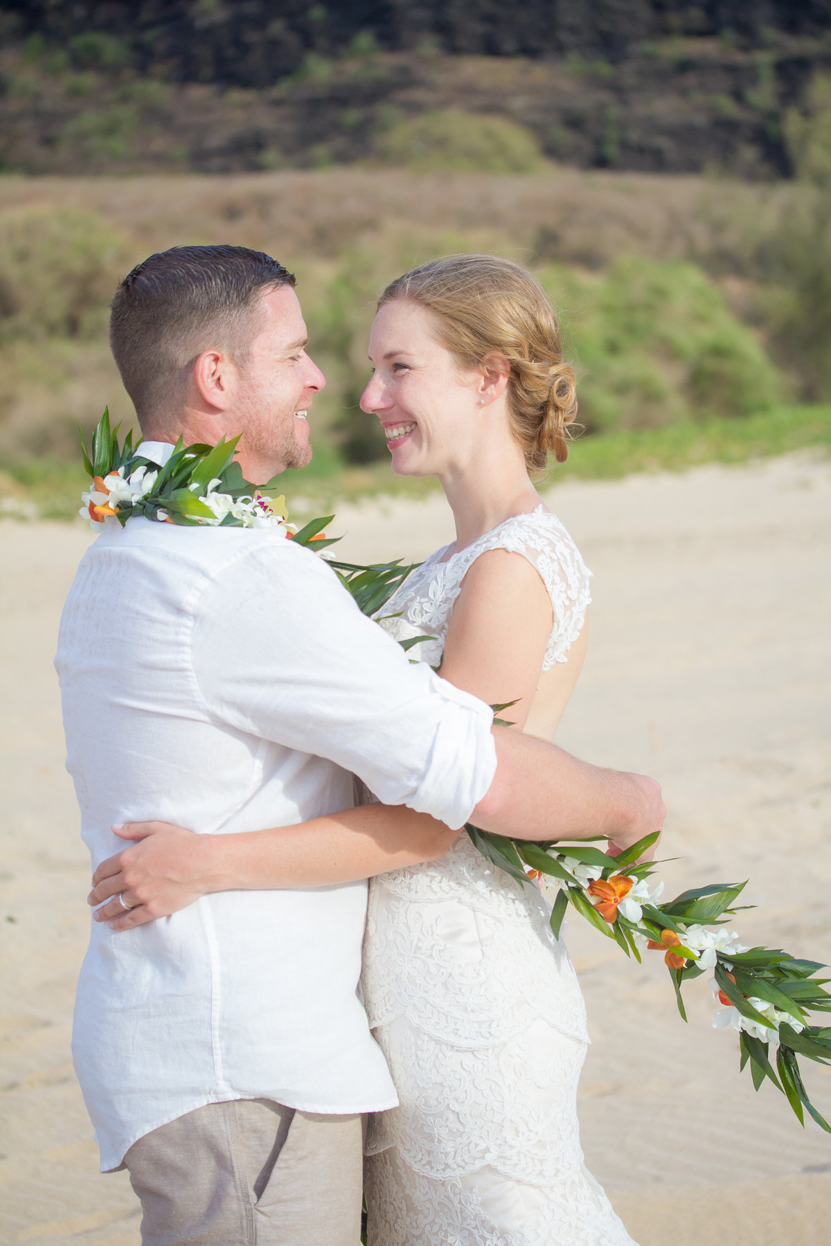 Bride and groom embrace during beach wedding in Kauai.
