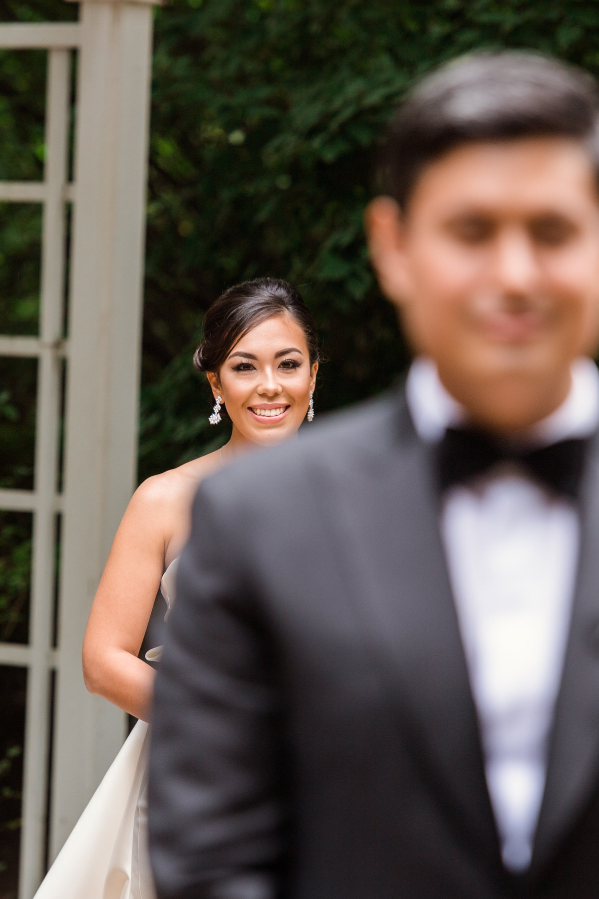 photo of brides smile with groom blurred out before first look during wedding at The Garden City Hotel