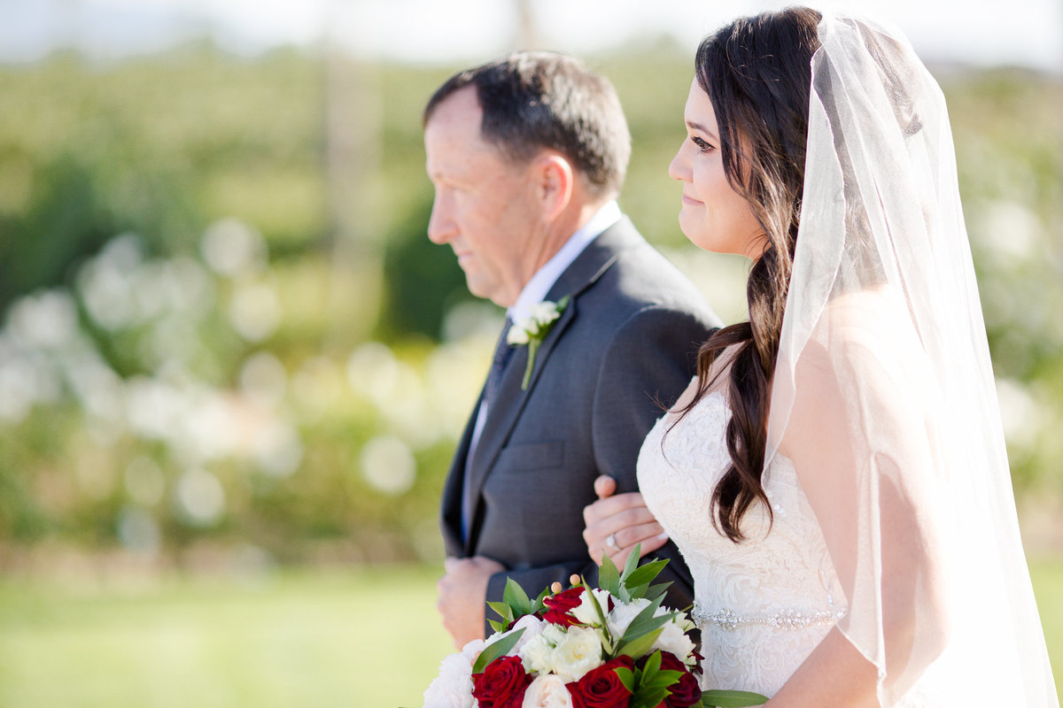 Bride holds back her tears as her father walks her down the aisle at her villa de amore wedding by matty fran photography