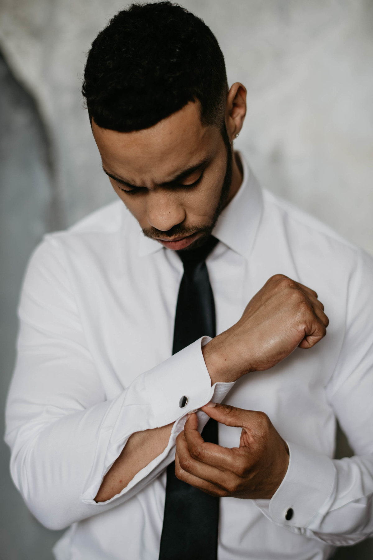 groom putting cufflinks in  suite