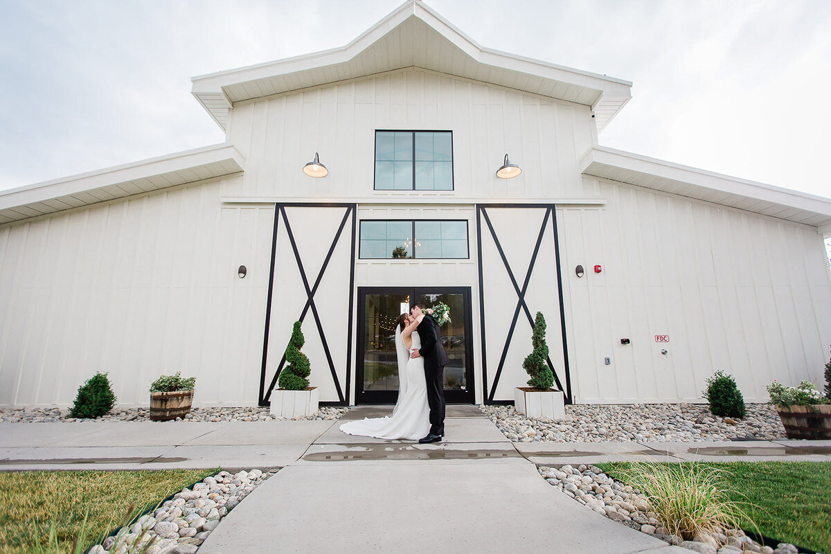 bride and groom kiss in front of white barn at woodlands