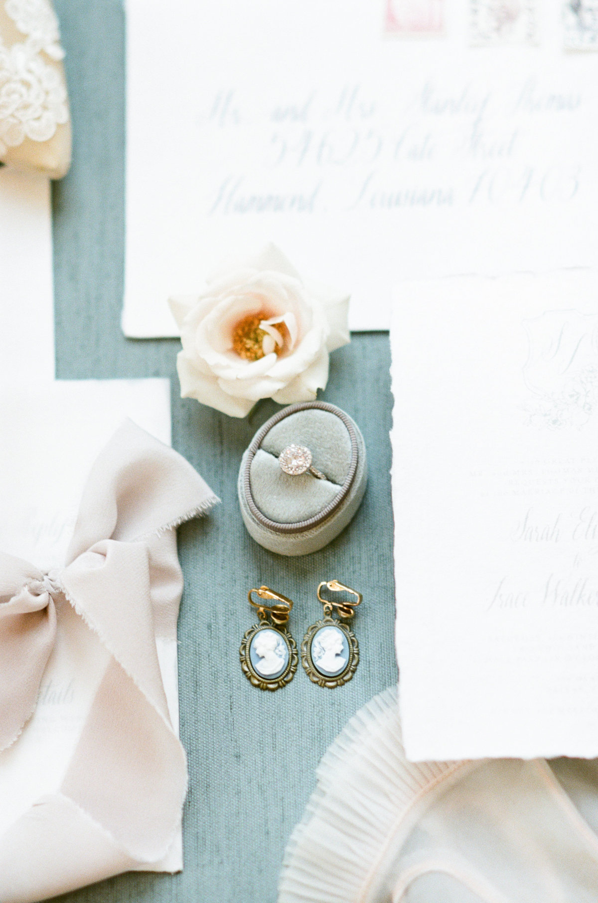 Flatlay of wedding stationery, earrings, and wedding details