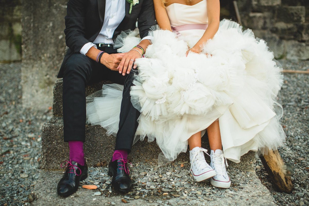 detail of bride and groom with converse shoes and vera wang wedding dress