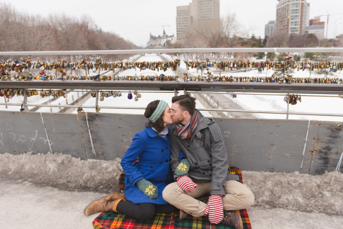 Engaged couple kissing under love lock bride by the Rideau Canal in Ottawa, Ontario