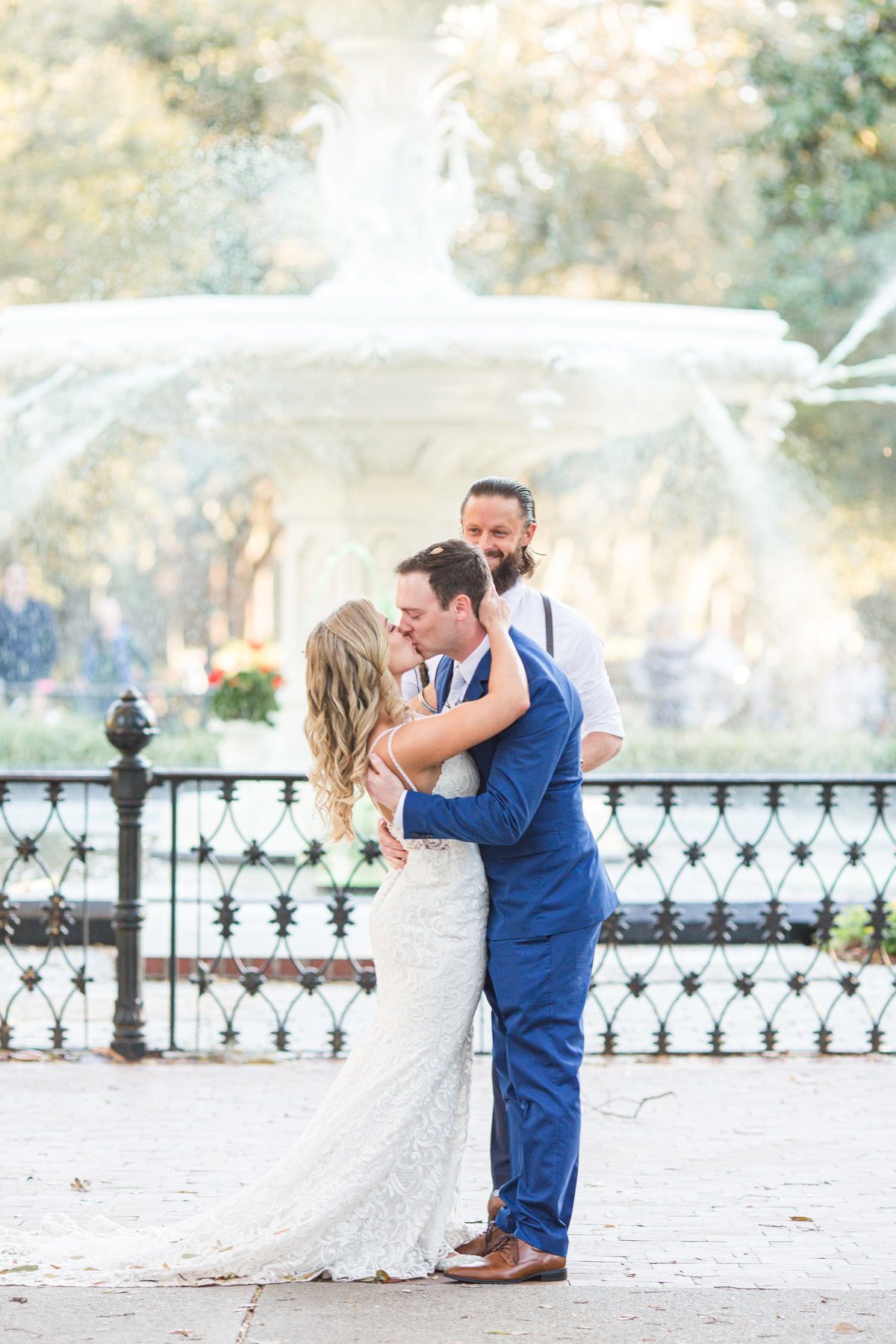 bride and groom first kiss in front of forsyth park fountain