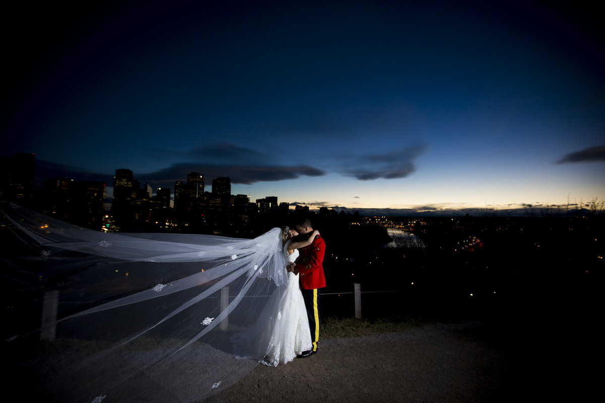 moody night portrait of bride and groom together in front of a dark sky. Dusk photo with flowing veil.
