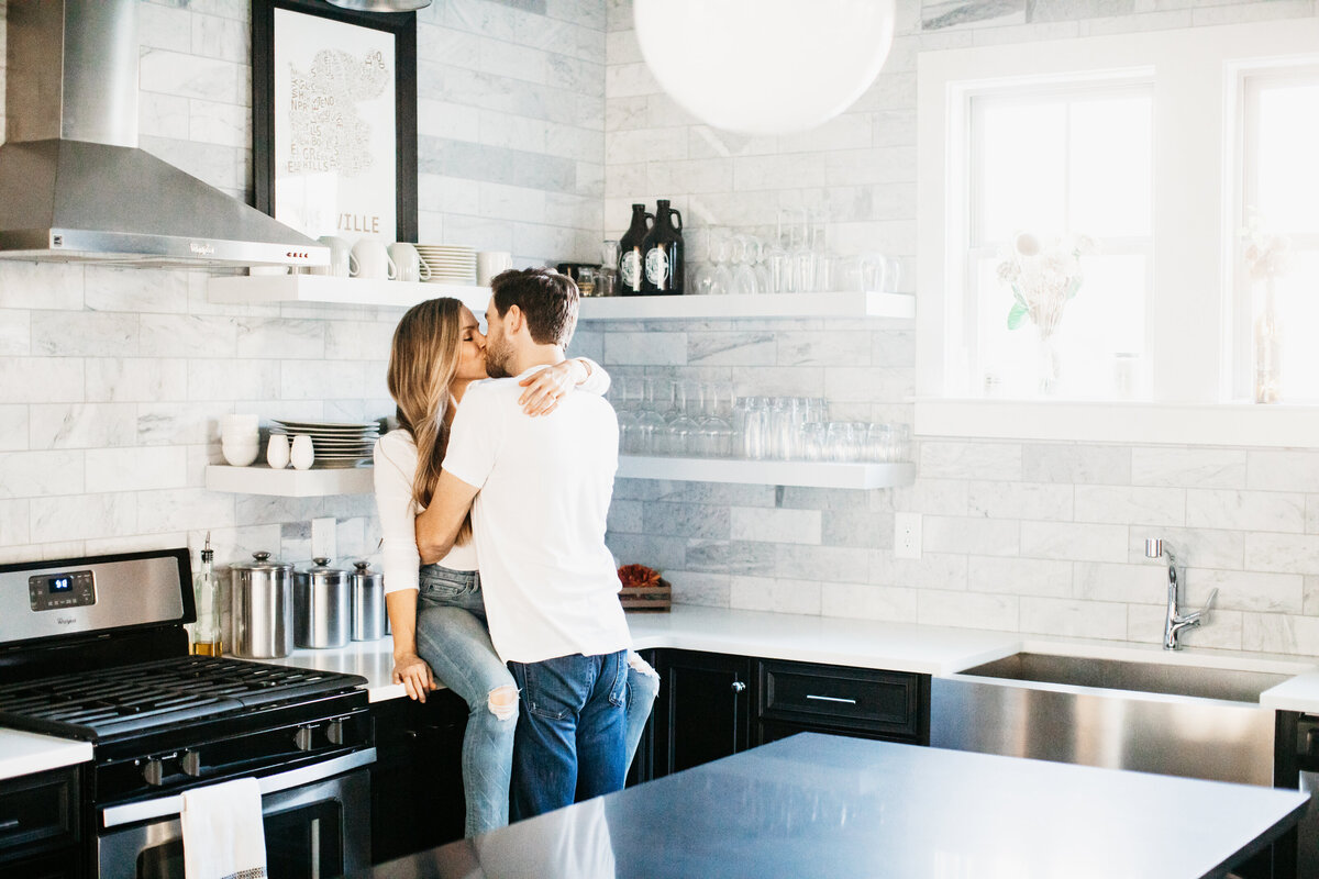 couple sitting on a countertop in a kitchen kissing in home