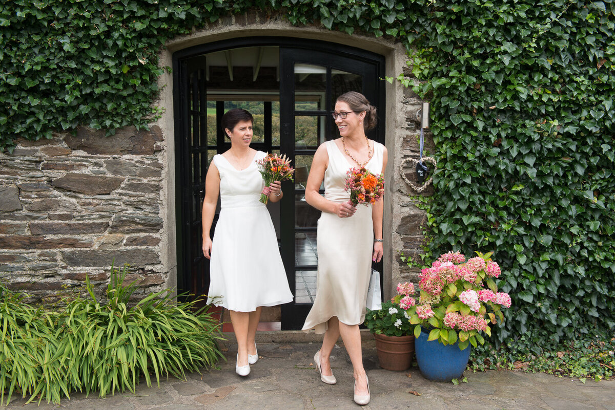 two brides wearing white dresses, walking and laughing while holding orange bouquets