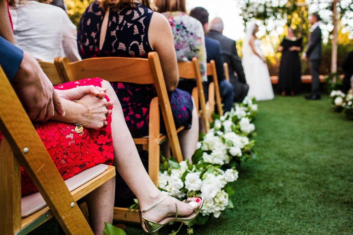 A couple holds hands while watching a ceremony during a Greenhouse Loft wedding.