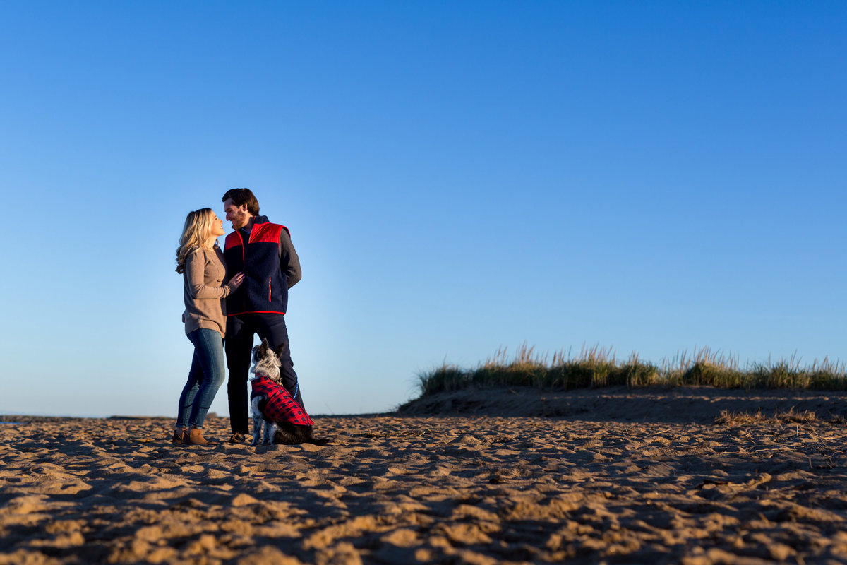 The couple laughs with their dog at the beaches of Plum Island MA