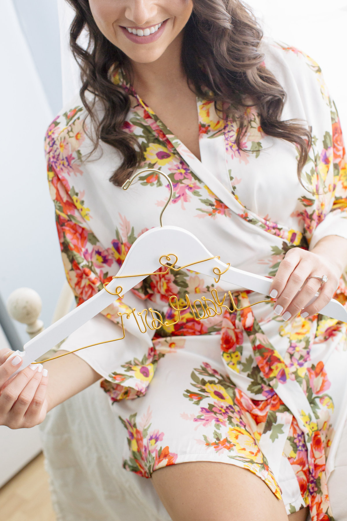 brides holding custom hanger in floral robe