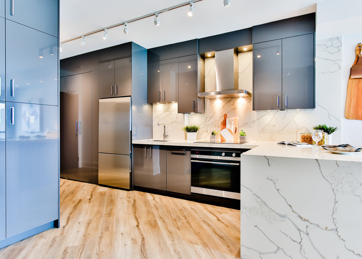 A luxury modern kitchen with gloss blue units and a white marble worktop is accented with wooden chopping boards.