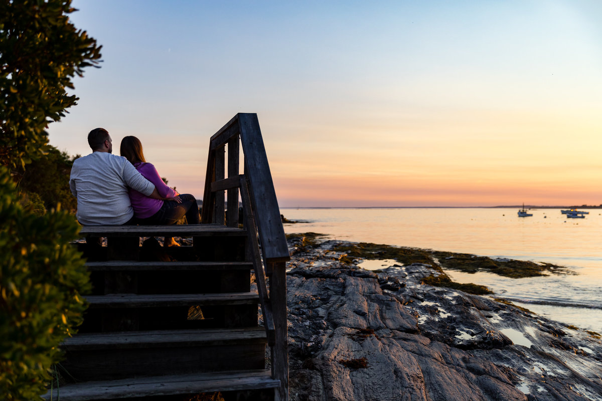 The couple sits on the wood stairs in Kettle Cove Maine