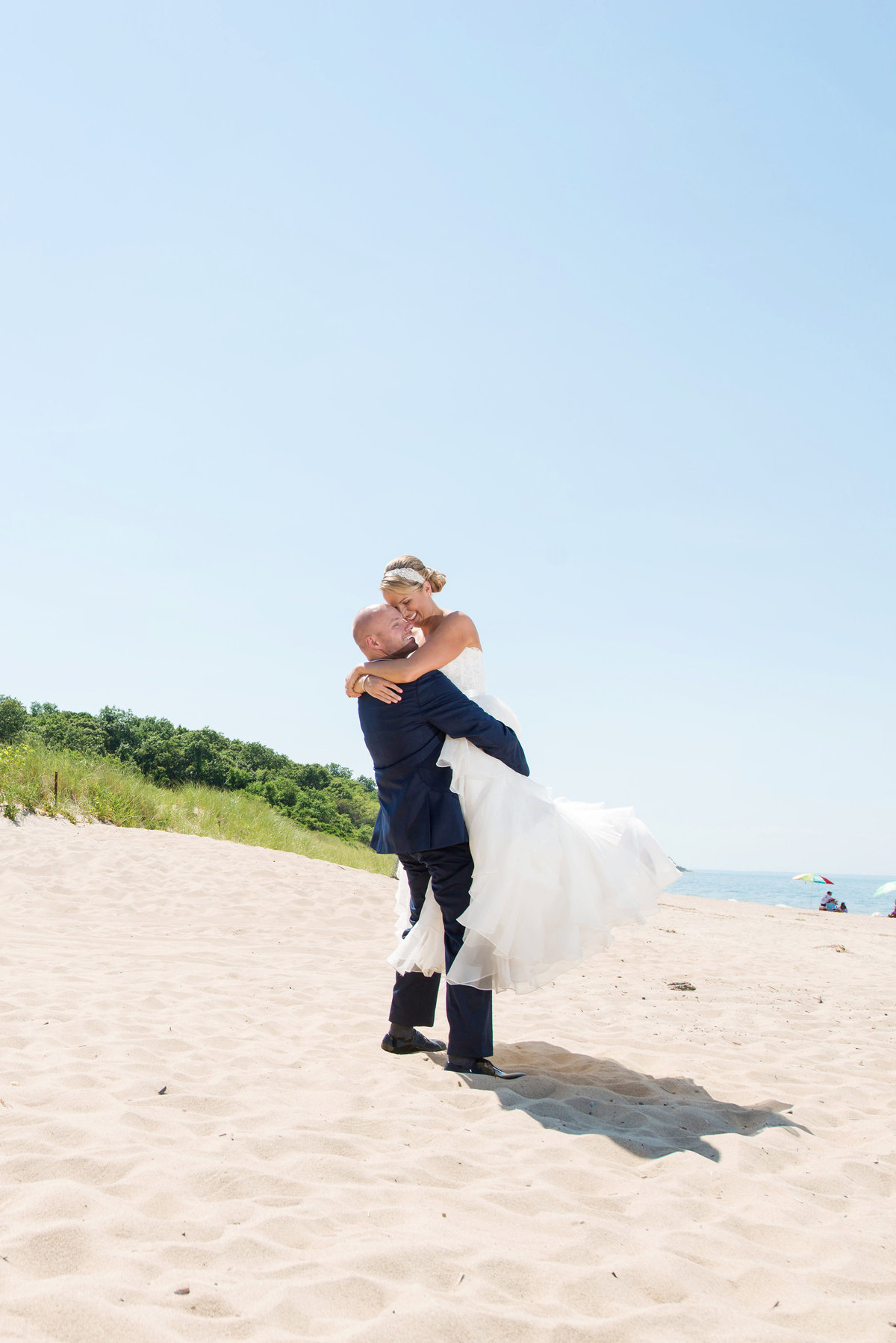 photo of groom carrying bride on the beach from wedding reception at Pavilion at Sunken Meadow