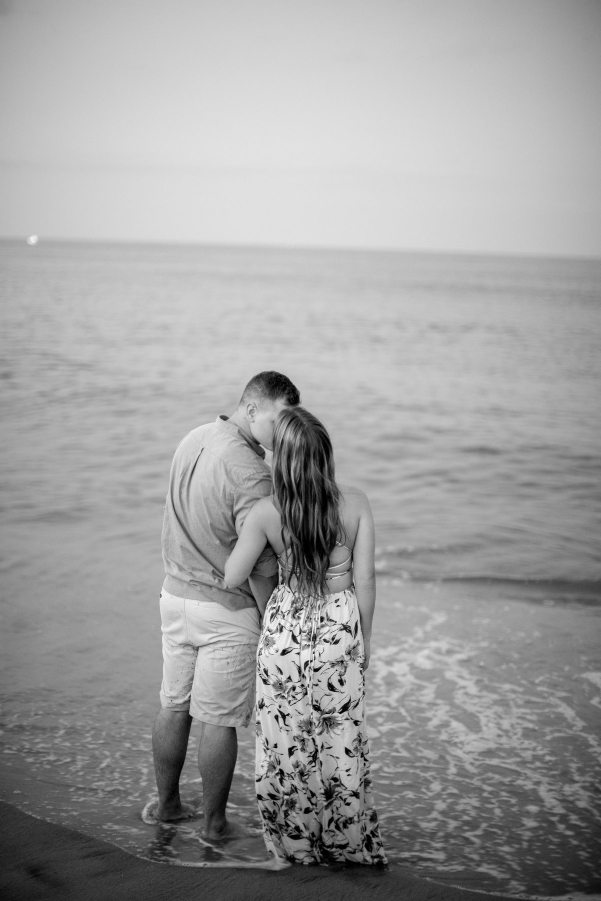 engaged couple kiss by the ocean at manasquan beach