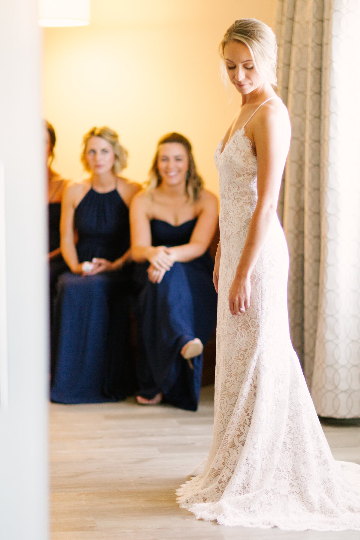 Bridesmaids look at bride as she gets ready for her wedding at Firestone Vineyard