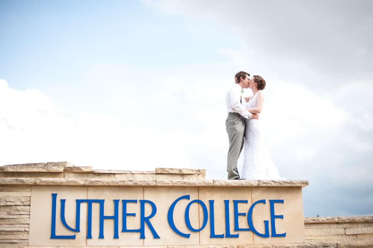 bride and groom standing on top of luther college sign