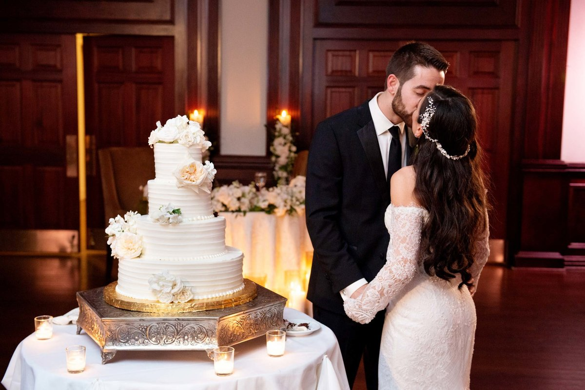 Bride and groom kissing next to their wedding cake at The Mansion at Oyster Bay