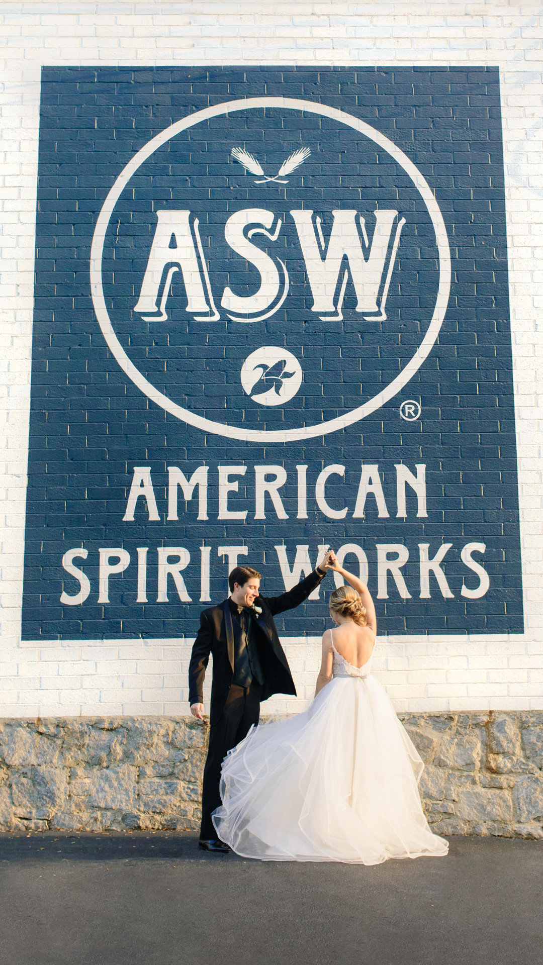 A bride and groom dances in the sunset outside of the Stave room at American Spirit Works