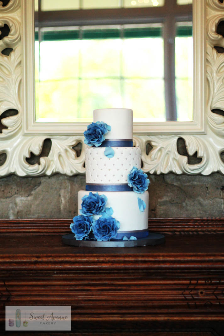elegant white wedding cake with blue vintage roses
