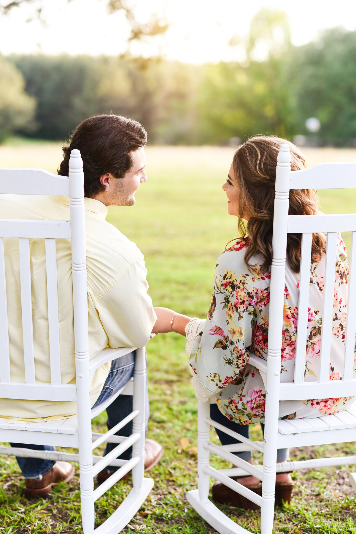 Beautiful Mississippi Engagement Photography: couple holding hands watches sunset from rocking chairs in Mississippi