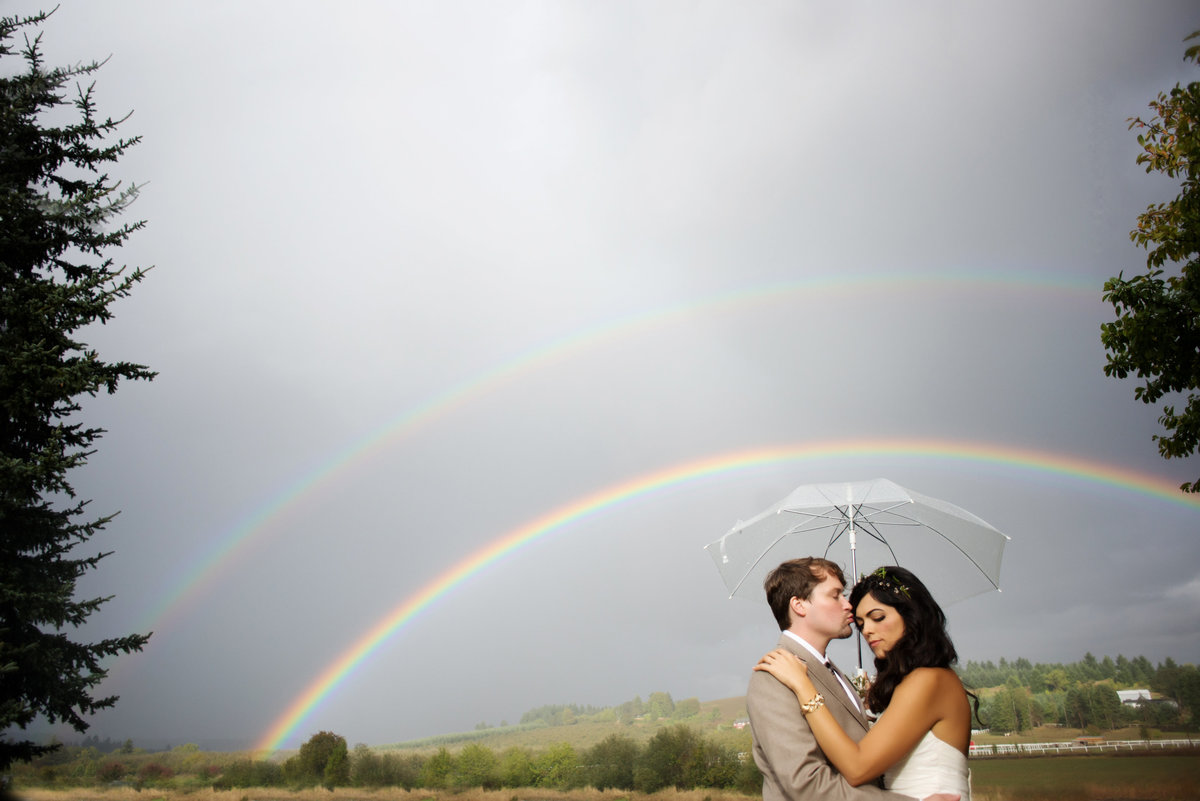 bride and groom kiss under a double rainbow at laurel ridge winery