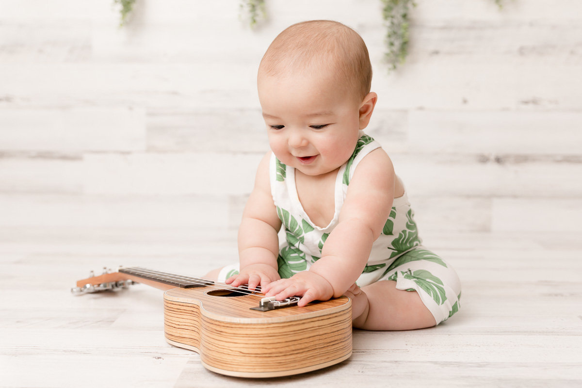 Seven month old plays with ukulele during studio sitter session