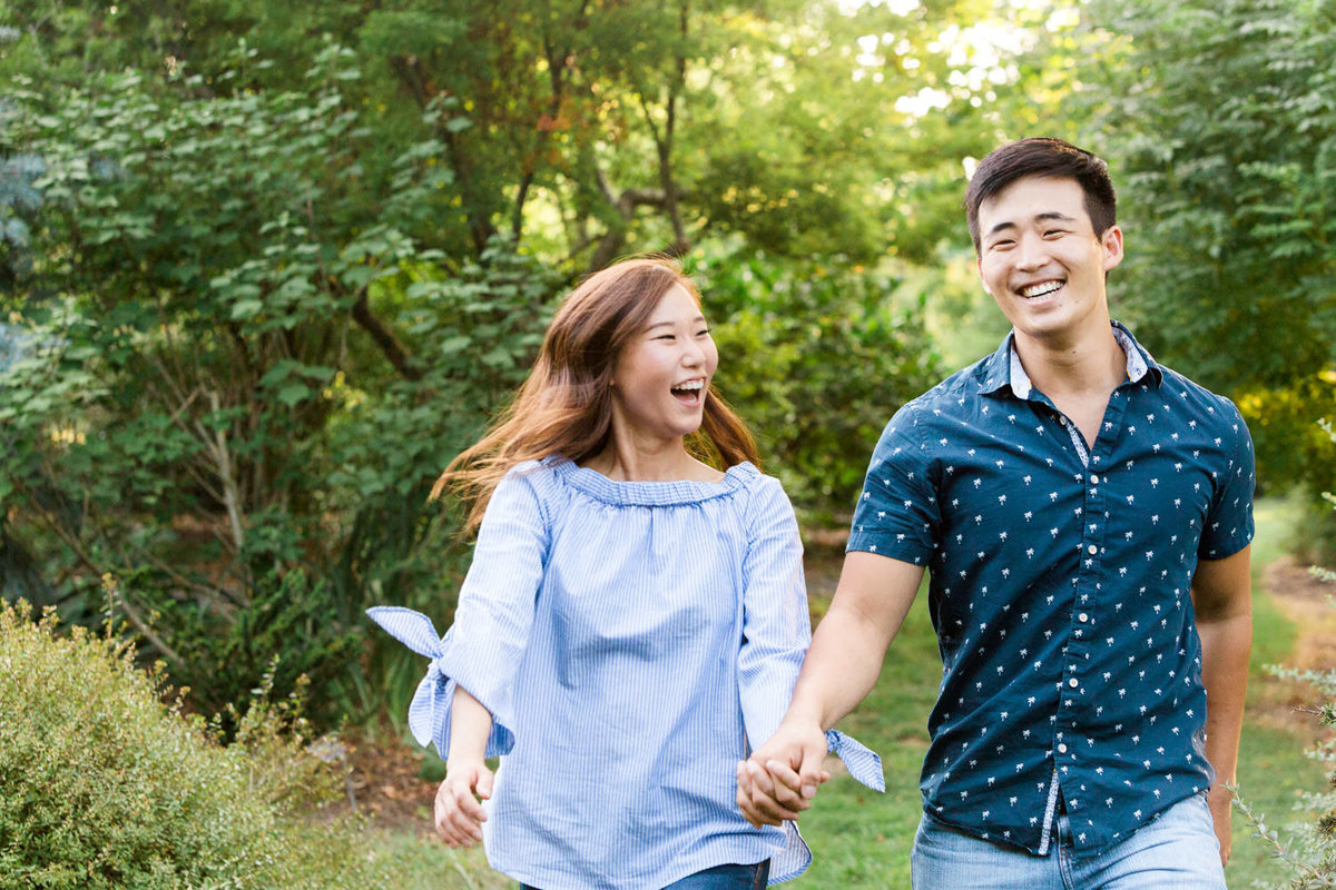 young couple laughs  surrounded by tree leaves