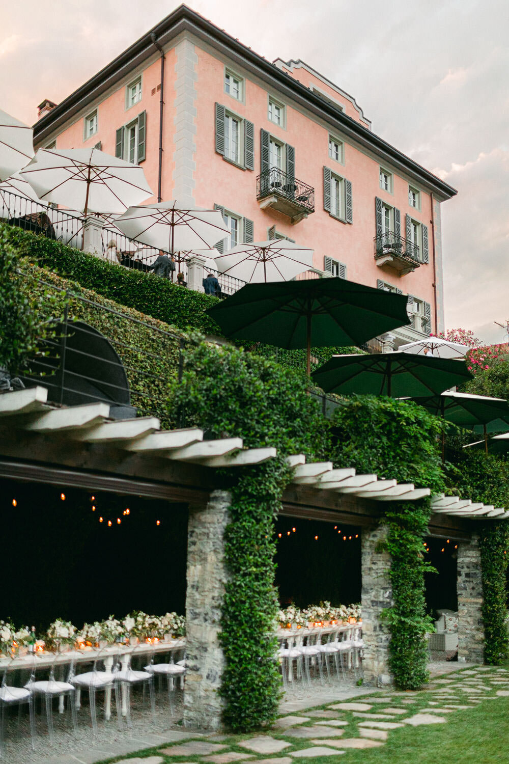 Lake Como Wedding Reception white florals long table under green roof and pink villa