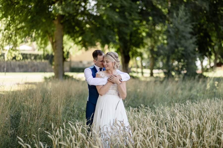 Groom hugging bride from behind in a meadow