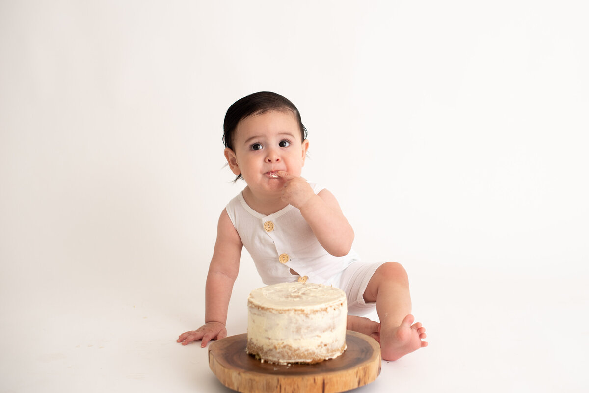 Boy not sure about his first birthday cake