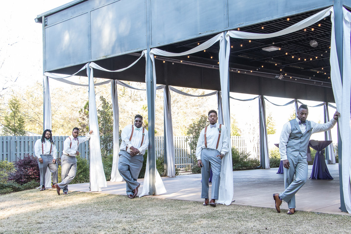 Groom and groomsmen leaning against pole