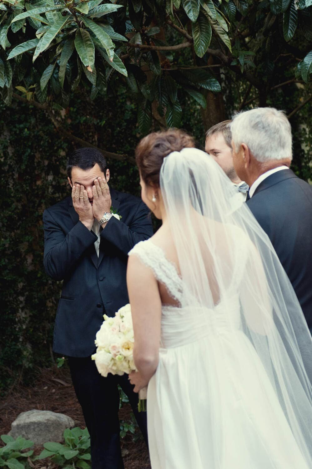 a groom cries and hides his face as his bride comes down the aisle