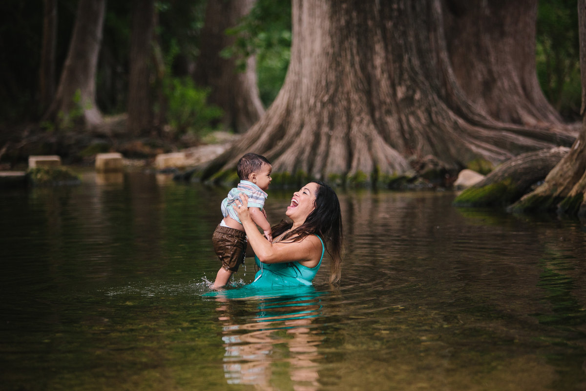 mother holding her son while sitting in a river
