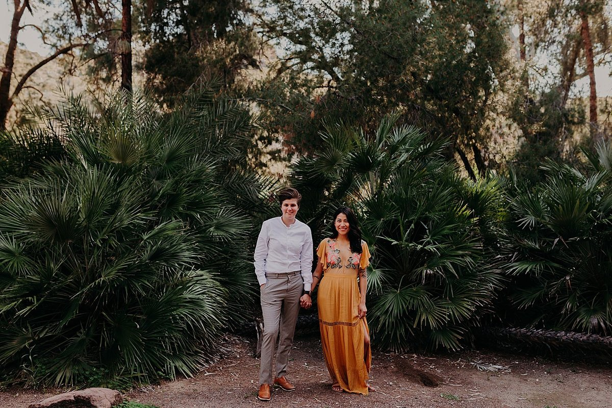 Two women take engagement photos at Boyce Thompson Arboretum in green jungle