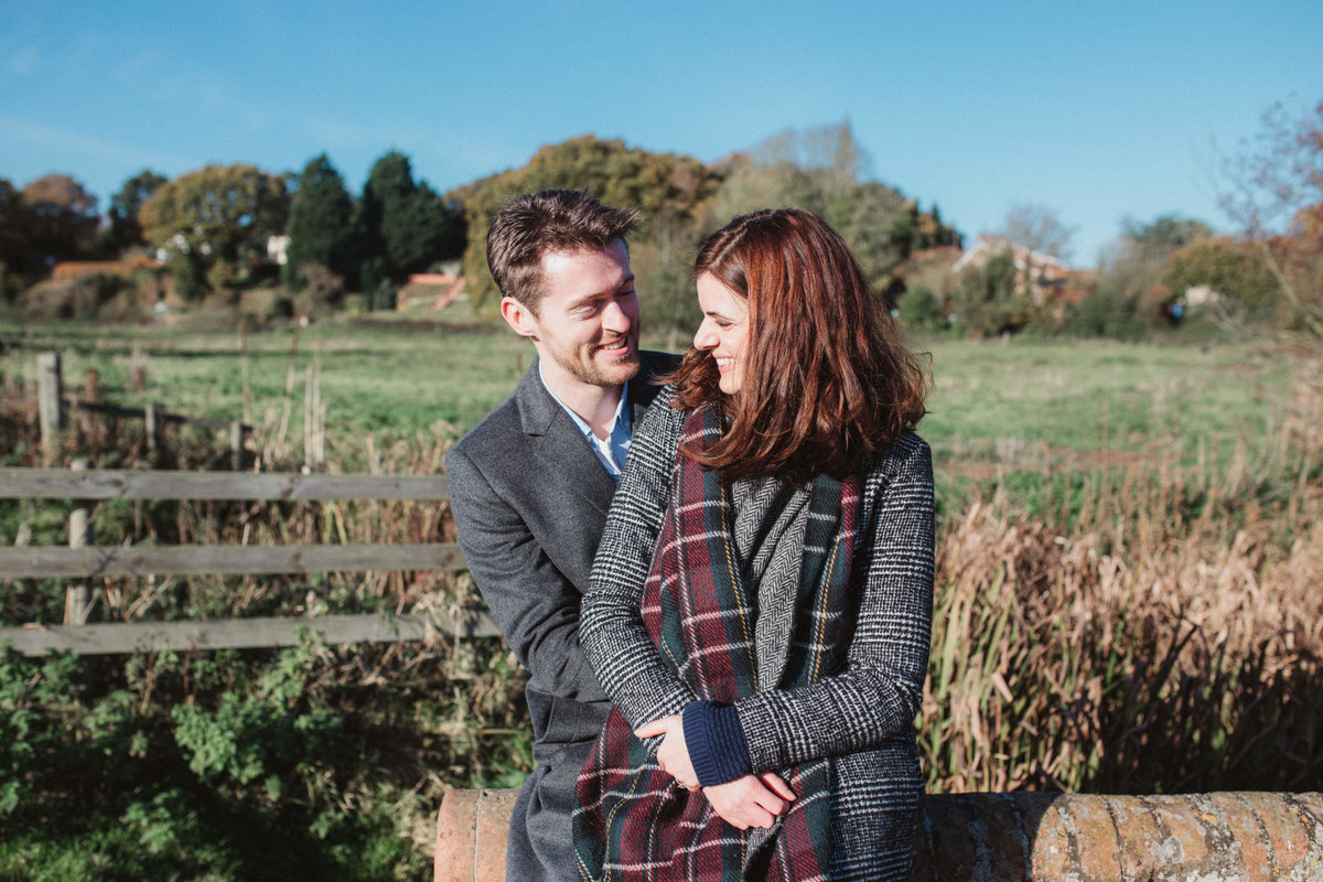 Photo of relaxed couple laughing and cuddling outside in the Norfolk countryside