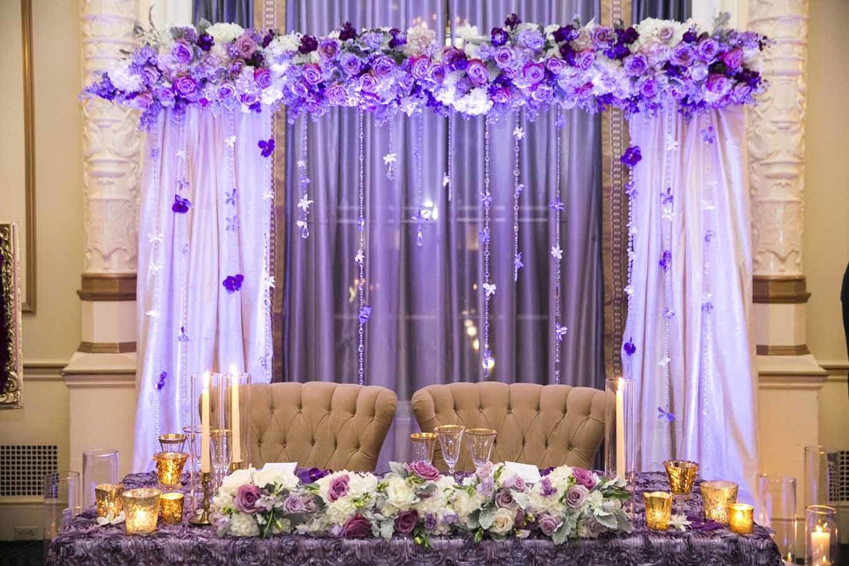 The head table was framed by a beautiful purple floral arch and strands of purple orchids.