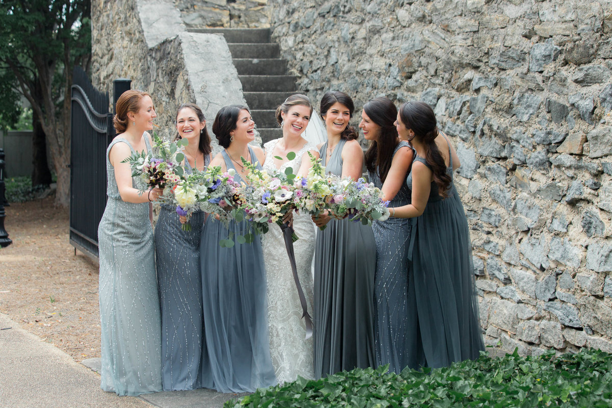 bridesmaid laughing by stone wall while Atlanta photographer takes a candid photo