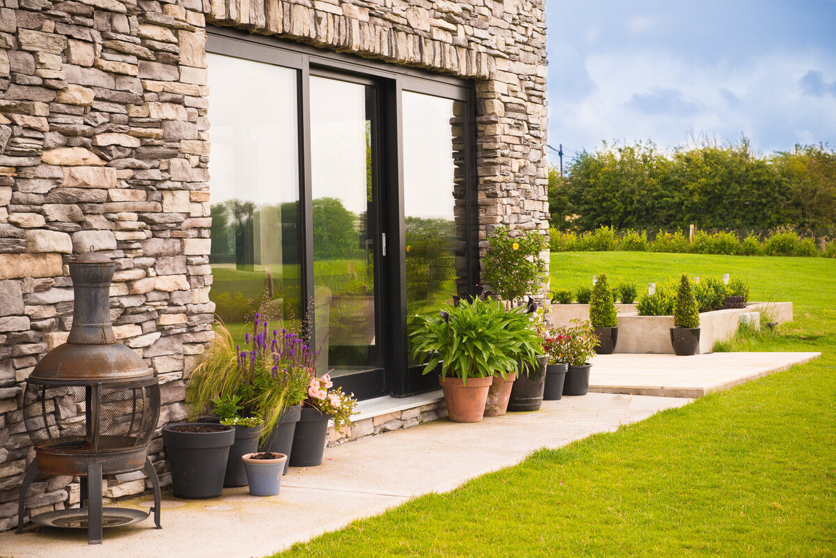 Exterior of sliding glass patio doors surrounded by exposed natural stone and potted plants
