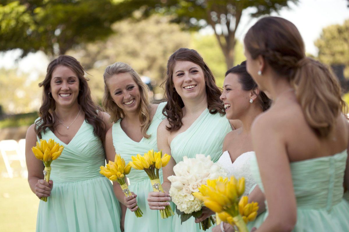 Bride with Bridesmaids in teal dresses holing yellow tulips