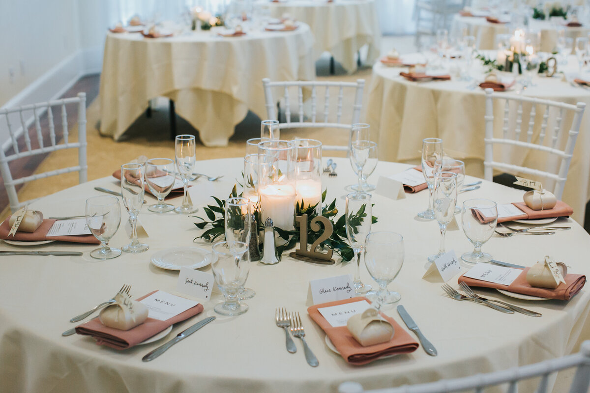 Guest tablescapes flicker with candles and soft greenery as they await their guests.