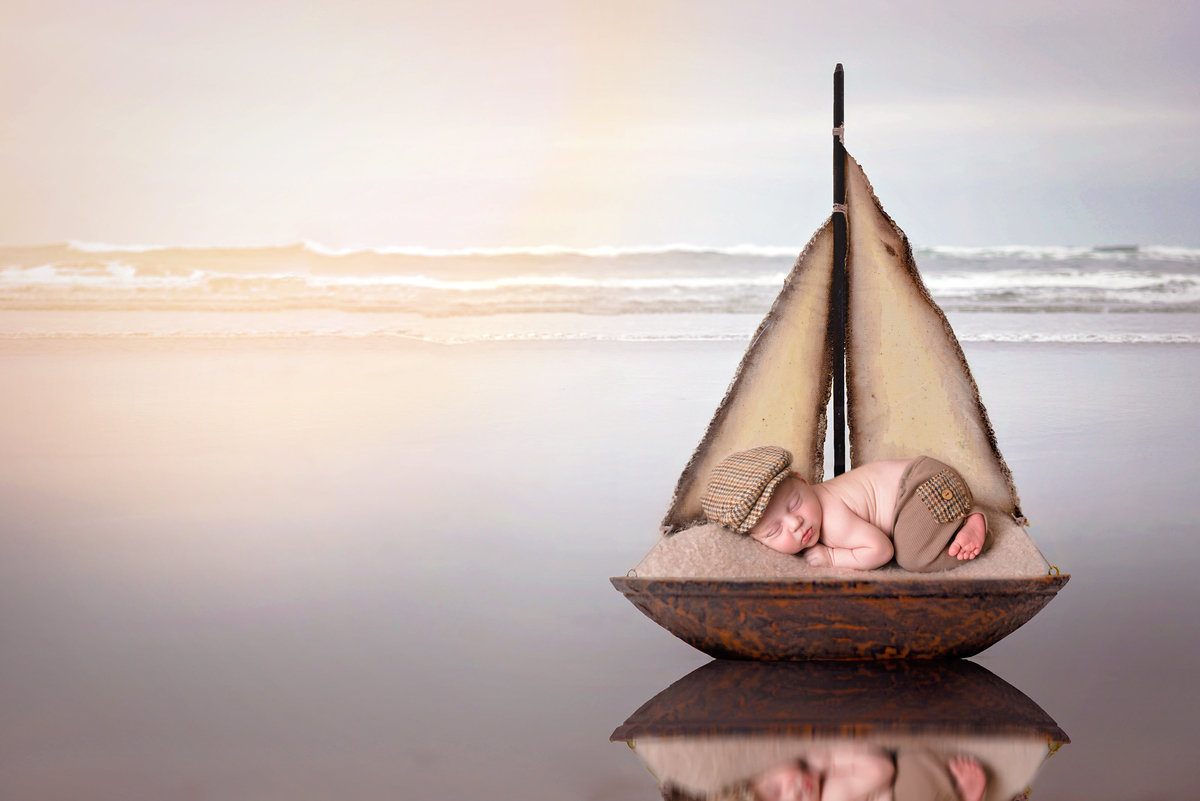 Newborn baby boy lying on a boat