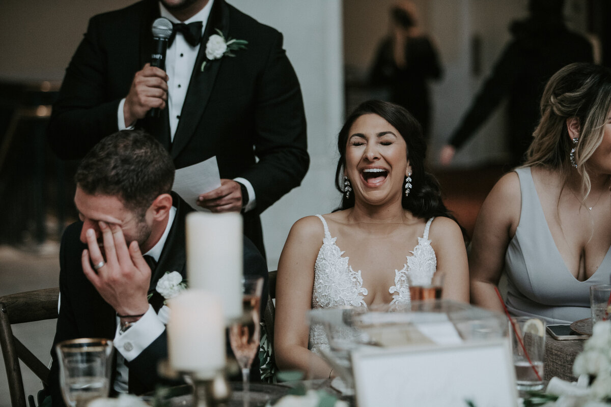 Bride and Groom laugh during wedding toast.