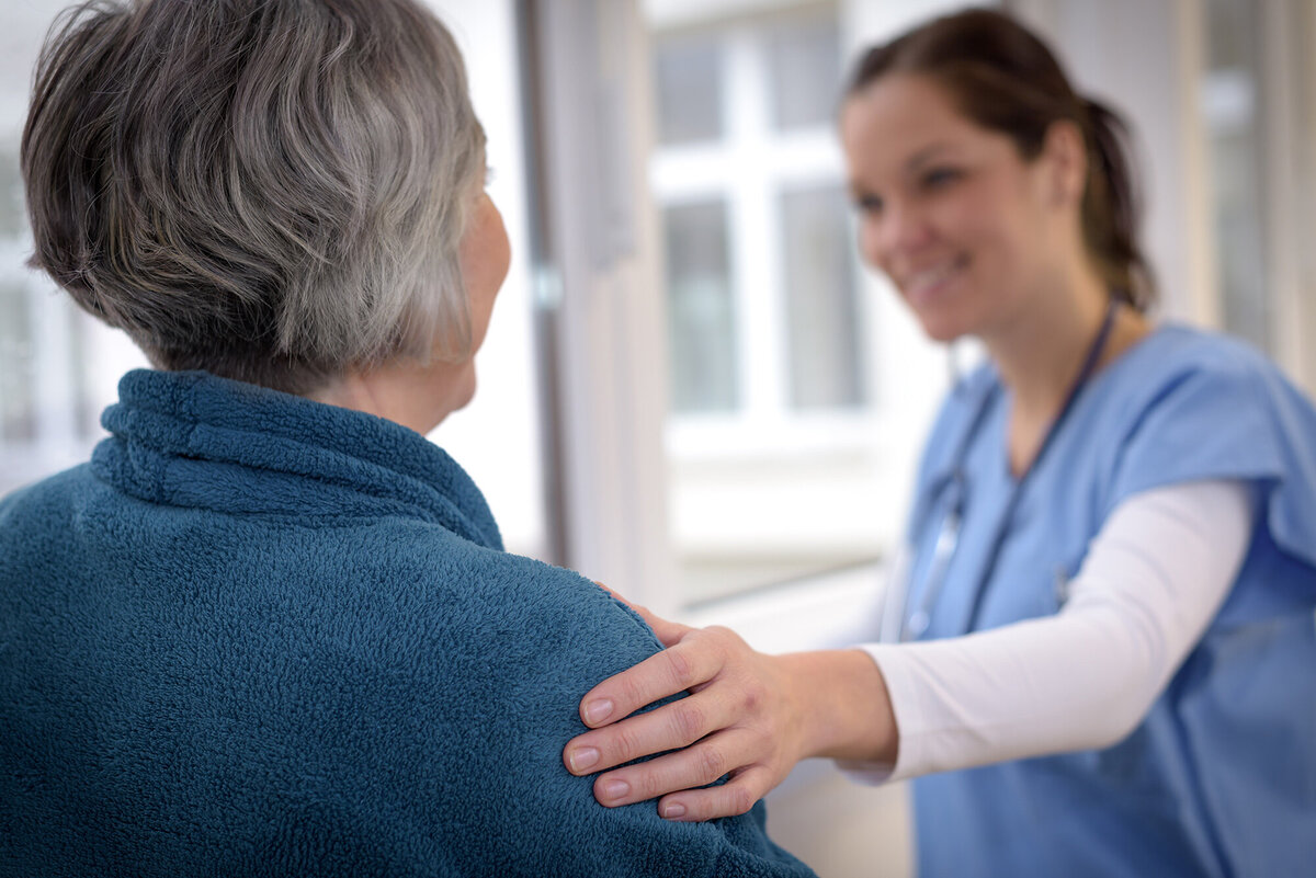 smiling-female-nurse-comforting-senior-patient-in-hospital-corridor