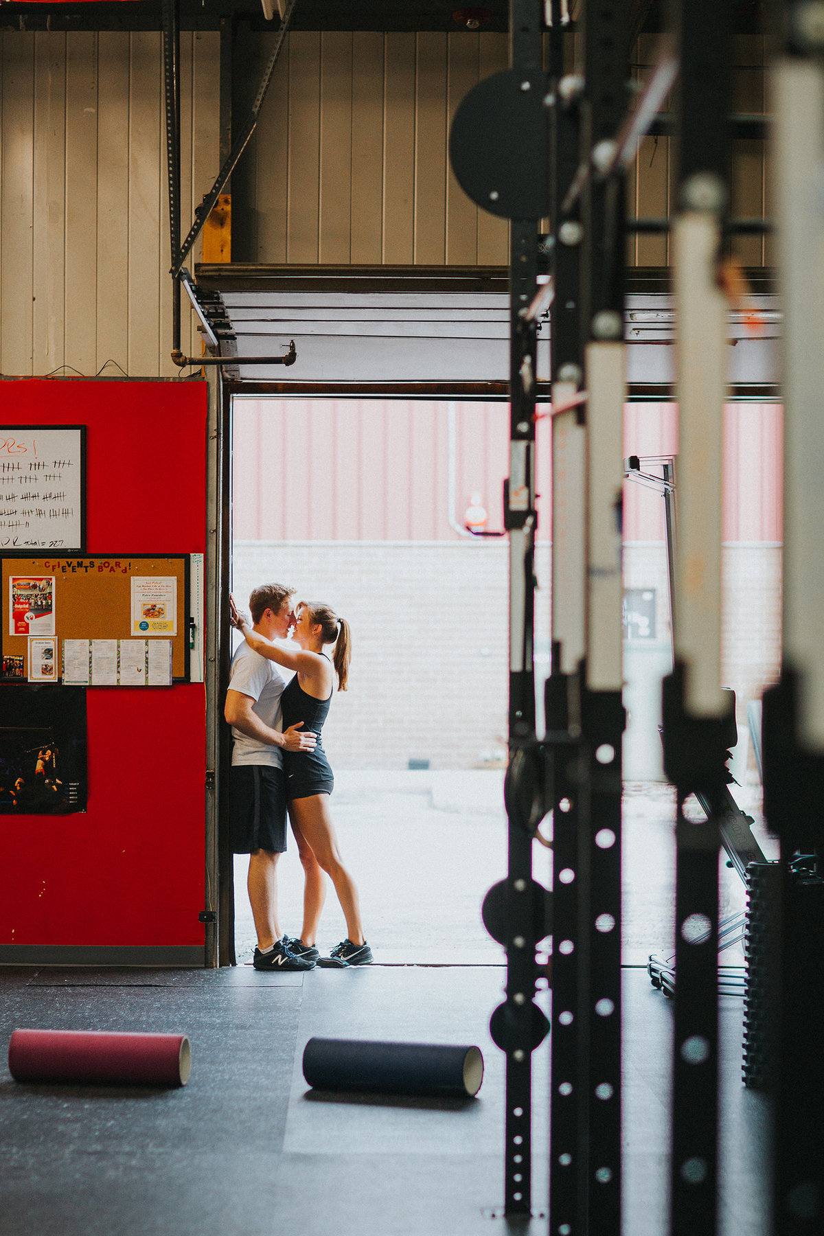 couple kissing during their engagement photography session at their crossfit gym